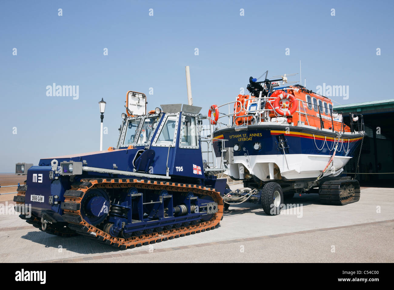 Lytham St Annes, Lancashire, England, UK. Lifeboat on wheeled trailer with tractor towing for crossing beach on - Stock Image