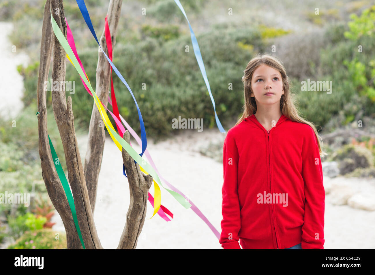 Girl standing near a decorated tree - Stock Image