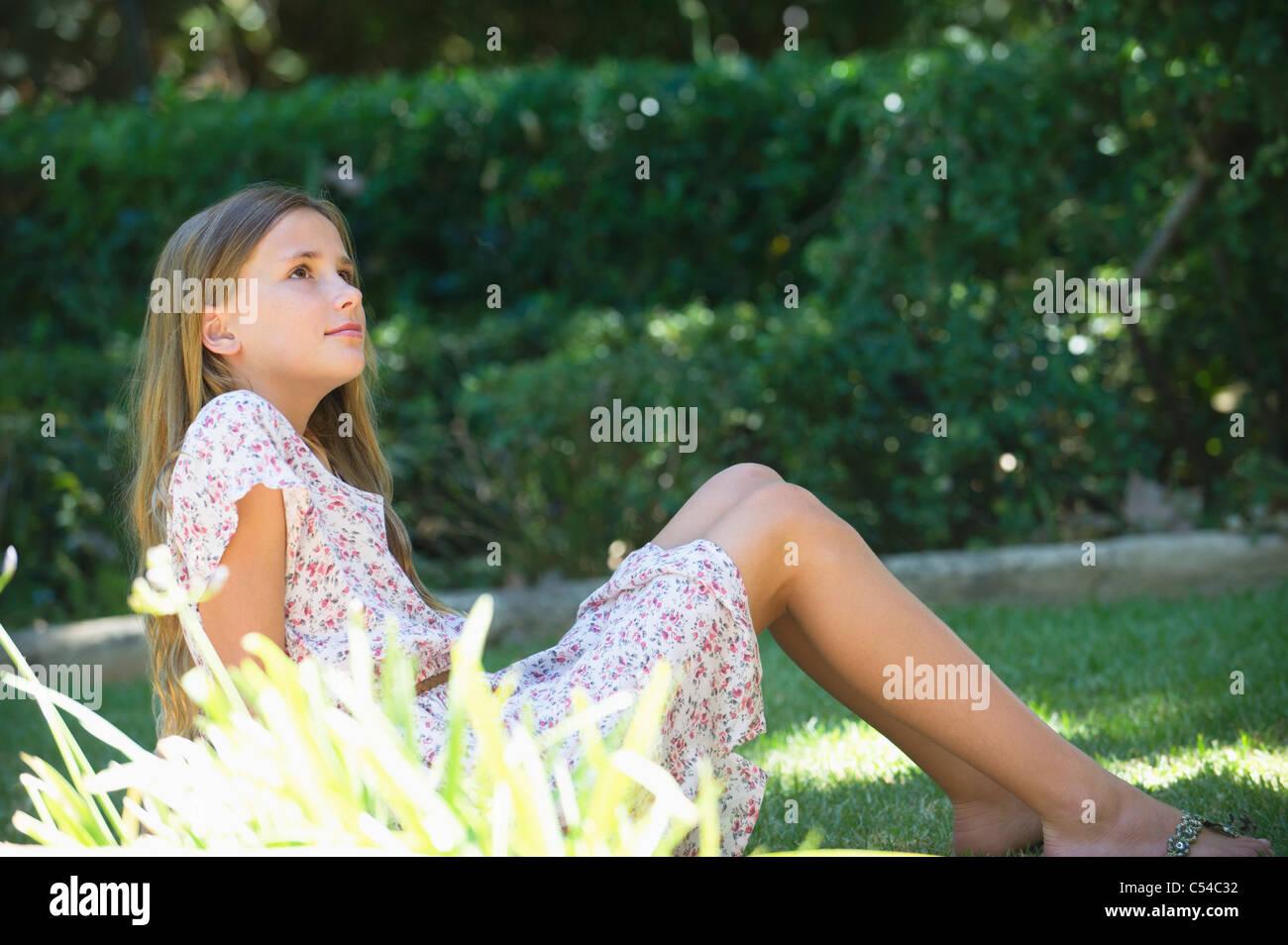 Contemplative little girl looking up in garden Stock Photo