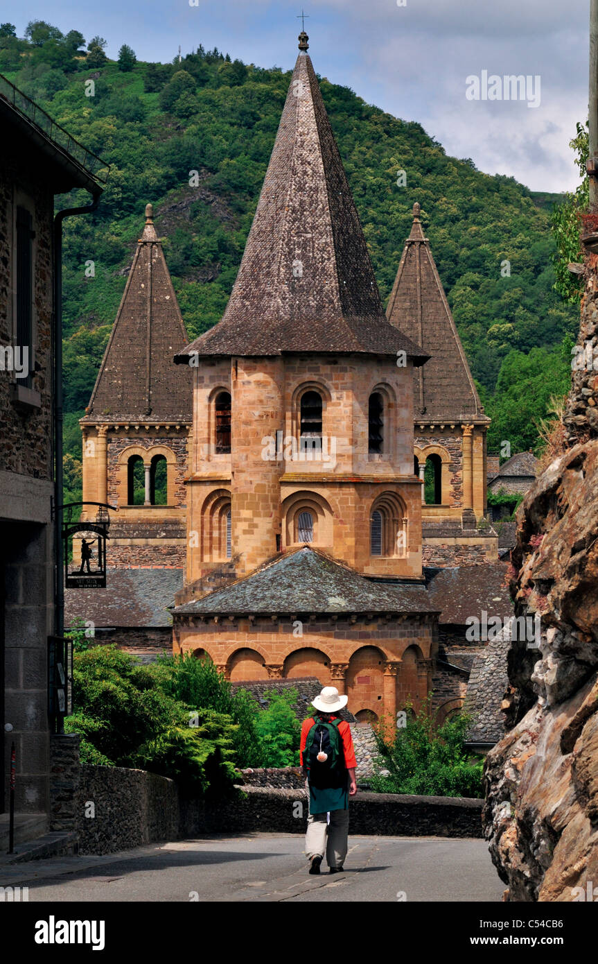 France, St. James Way: Pilgrim walking in direction of the Abbey St. Foy in the village center of Conques - Stock Image