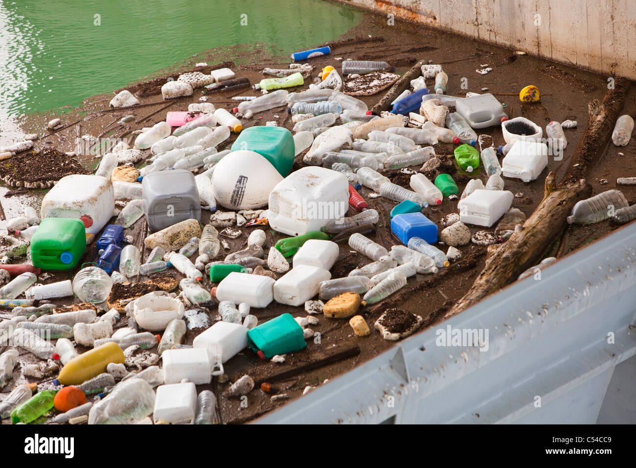 Plastic rubbish floating up agains the dam wall of the Iznajar hydro electric power station near Antequera in Andalucia, - Stock Image