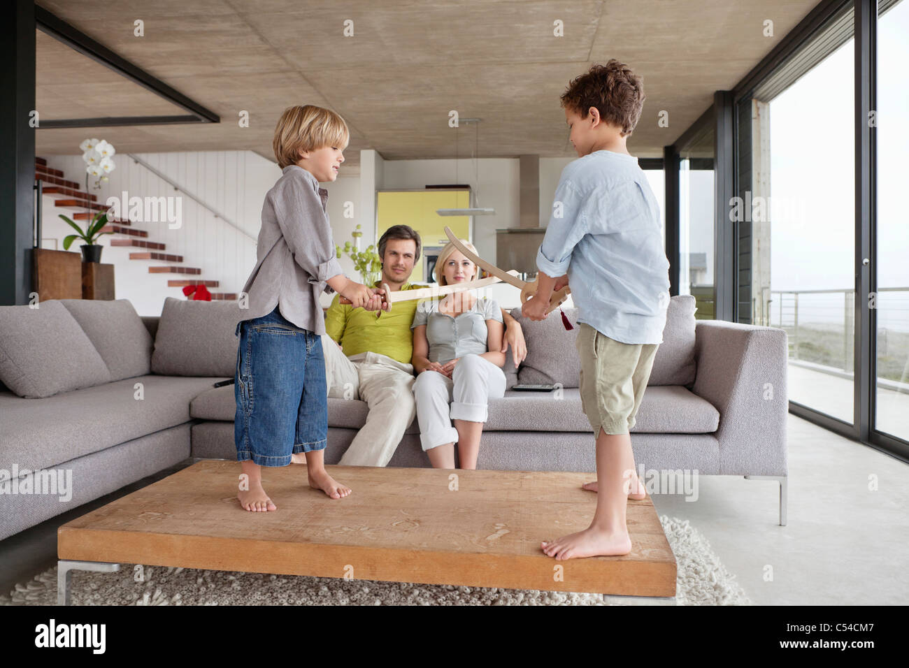 Boys playing with their parents sitting on a couch - Stock Image