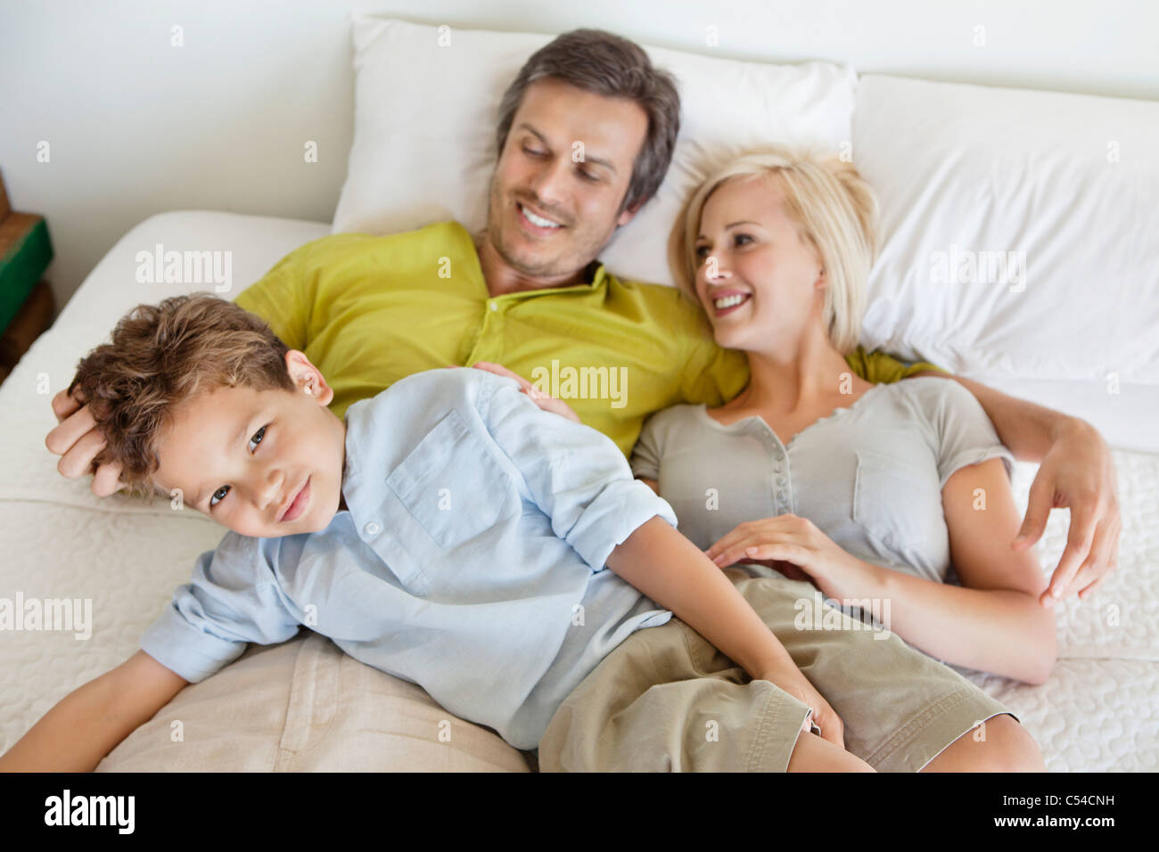 Parents with their son relaxing in bed - Stock Image