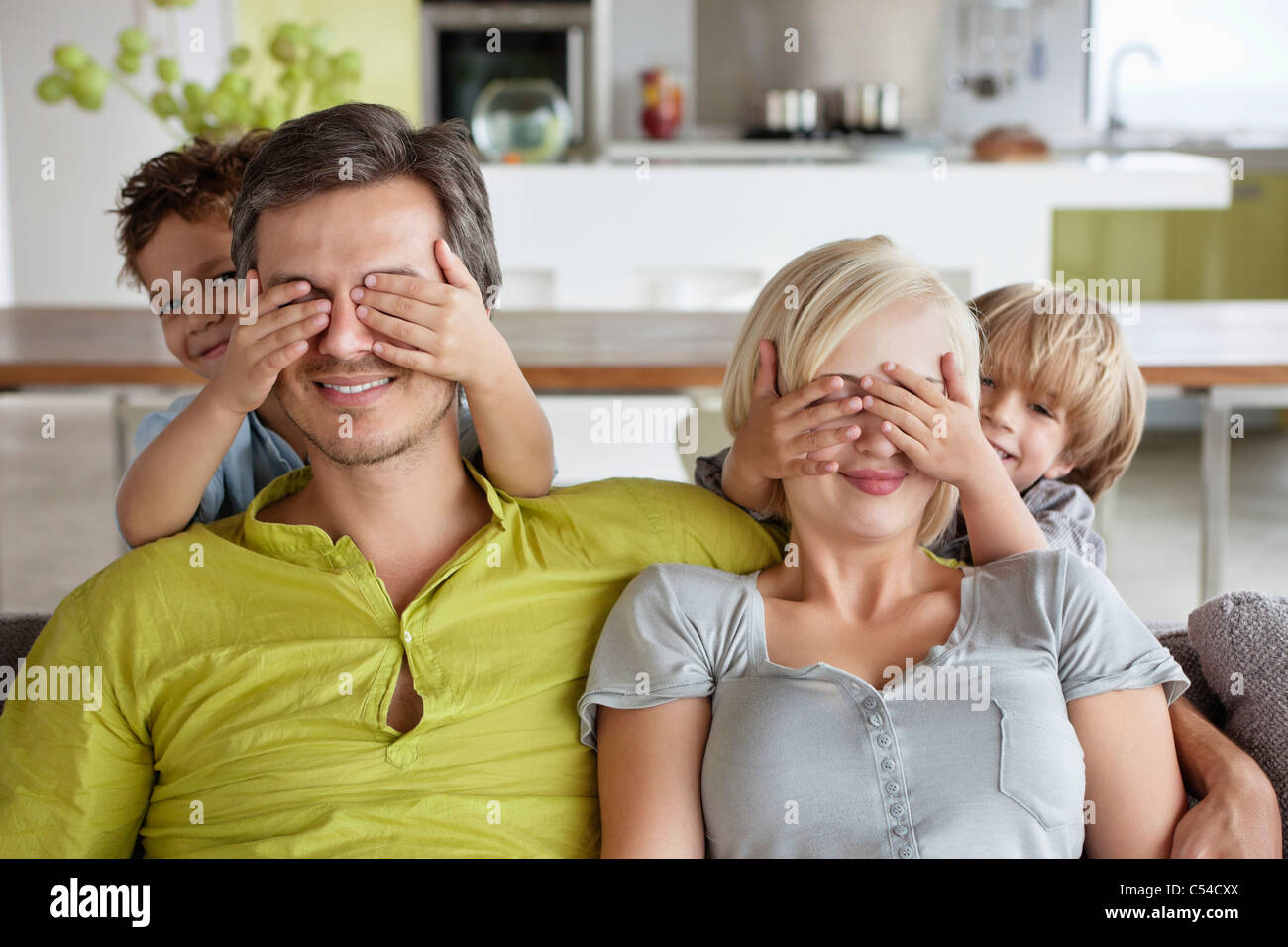 Children covering parents eyes - Stock Image