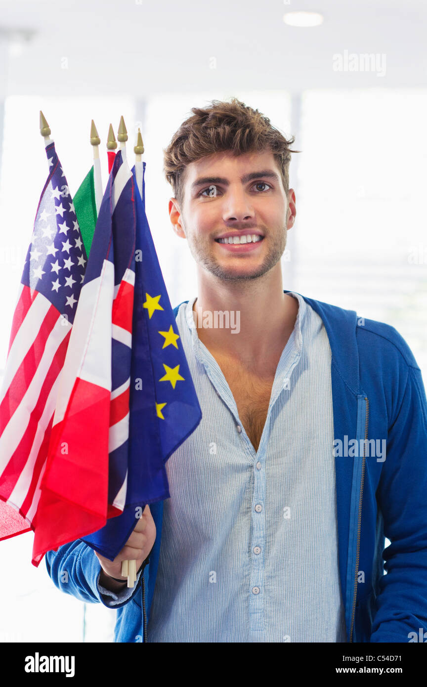 Portrait of a man holding flags of various countries at an airport - Stock Image