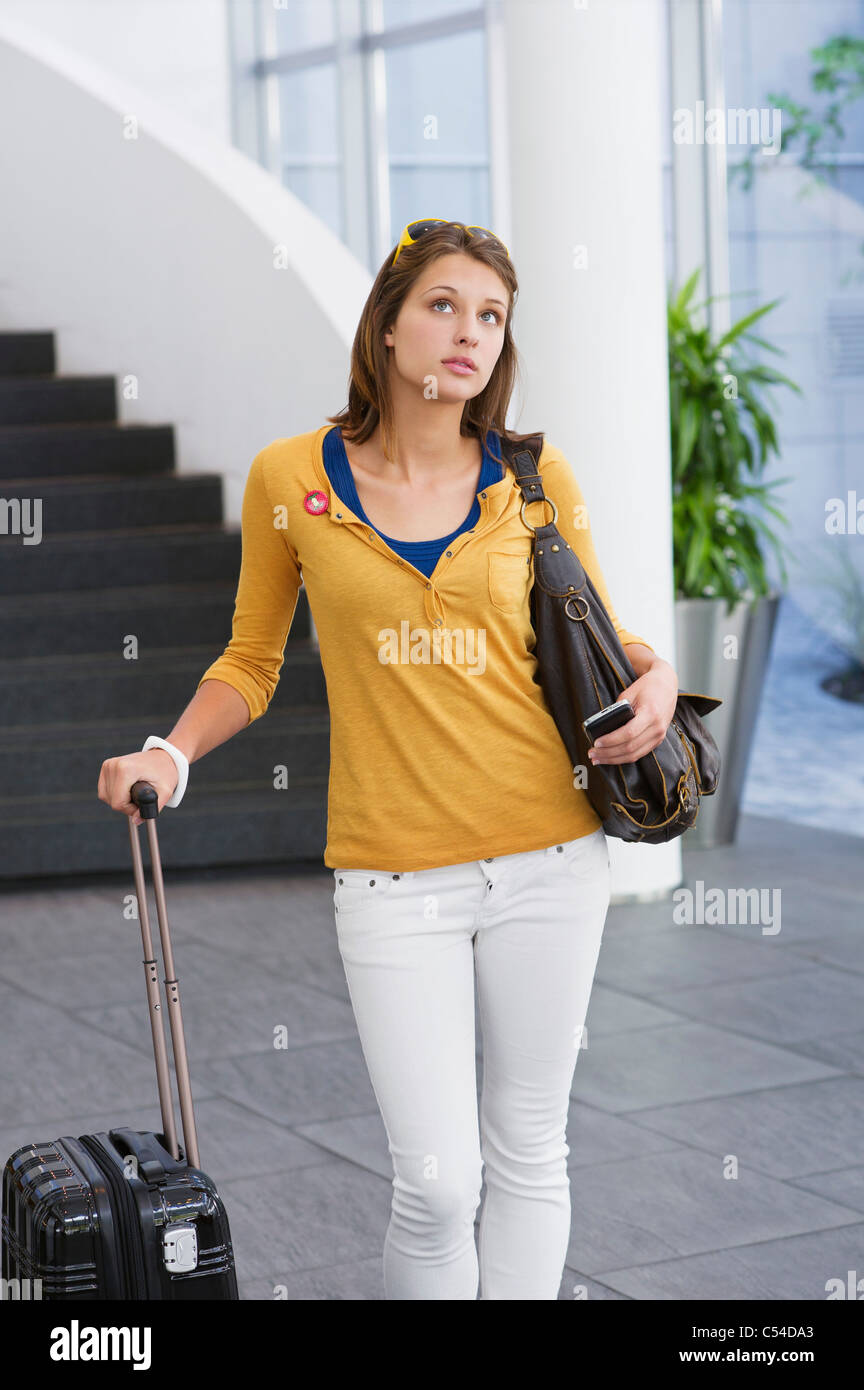 Woman holding a mobile phone and a trolley bag - Stock Image