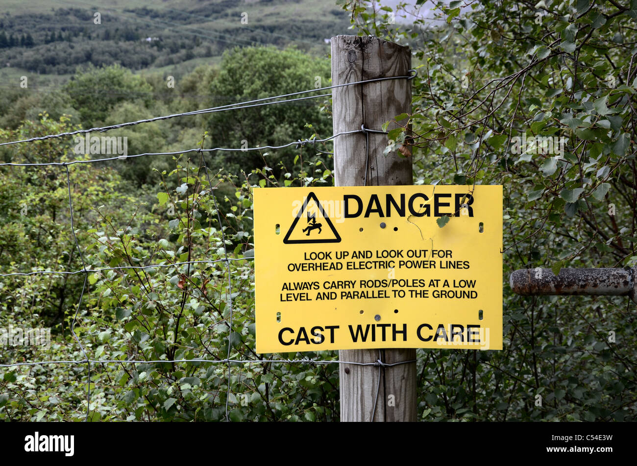Warning sign for fishermen alerting them to the danger of overhead electric power lines near Kinlochleven. - Stock Image
