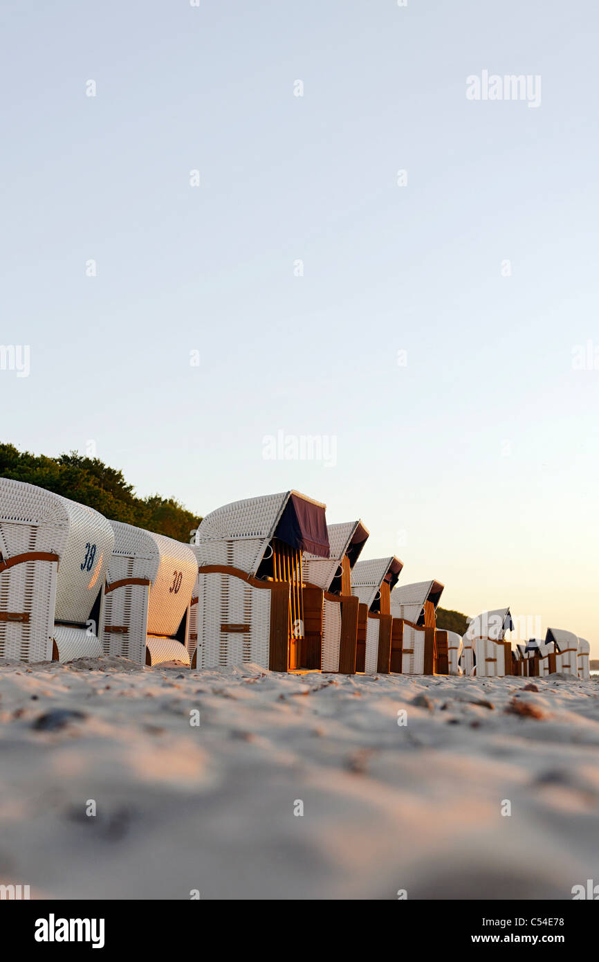 Roofed wicker beach chairs, beach, Baltic Sea, sunset, seaside resort of Ostseeheilbad Heiligendamm, Germany - Stock Image