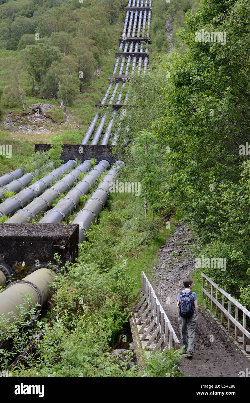 A walker on the path beside the pipeline which runs from Blackwater Reservoir down to Kinlochleven in Lochaber, - Stock Image