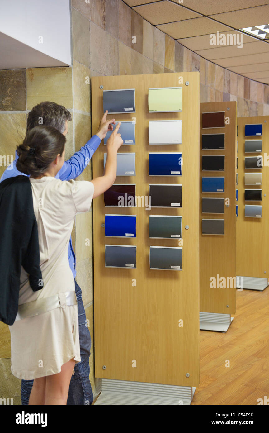 Rear view of a couple looking at color samples at car showroom - Stock Image