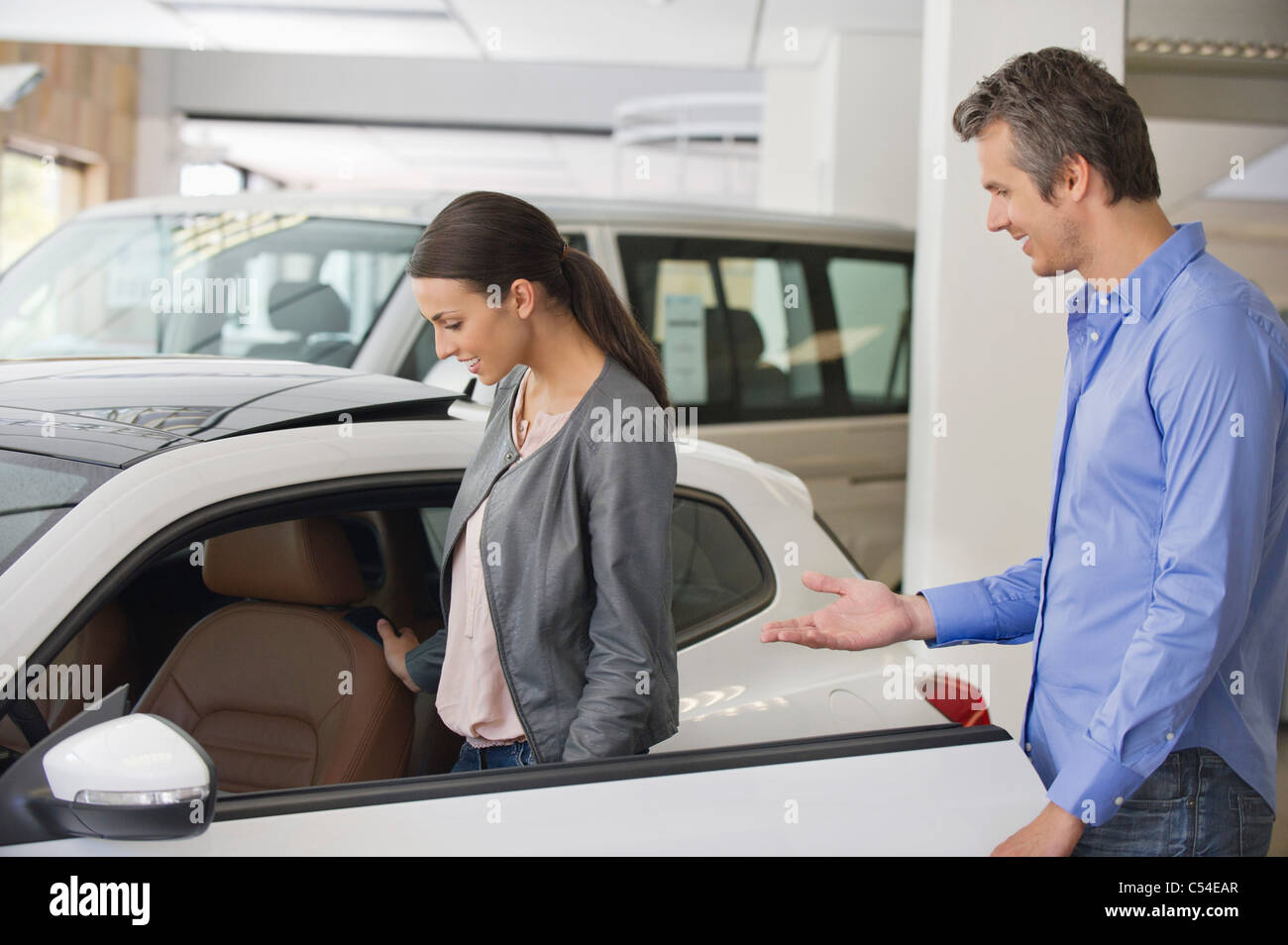 Young woman checking car from inside while man holding the door - Stock Image