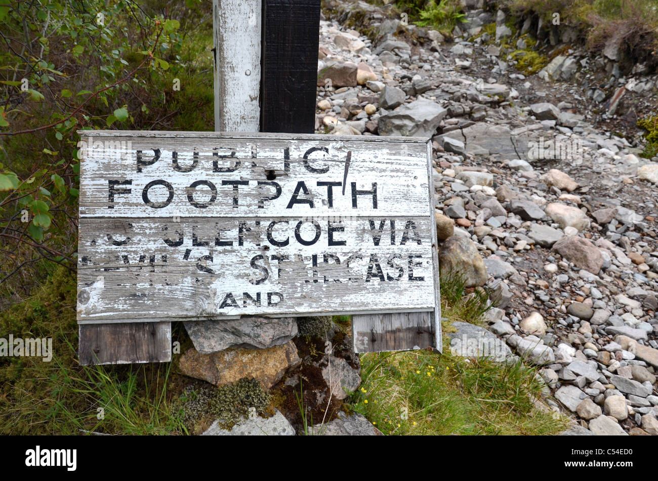 A rather weathered sign on part of the West Highland Way marking the path to Glencoe and the Devil's Staircase. - Stock Image