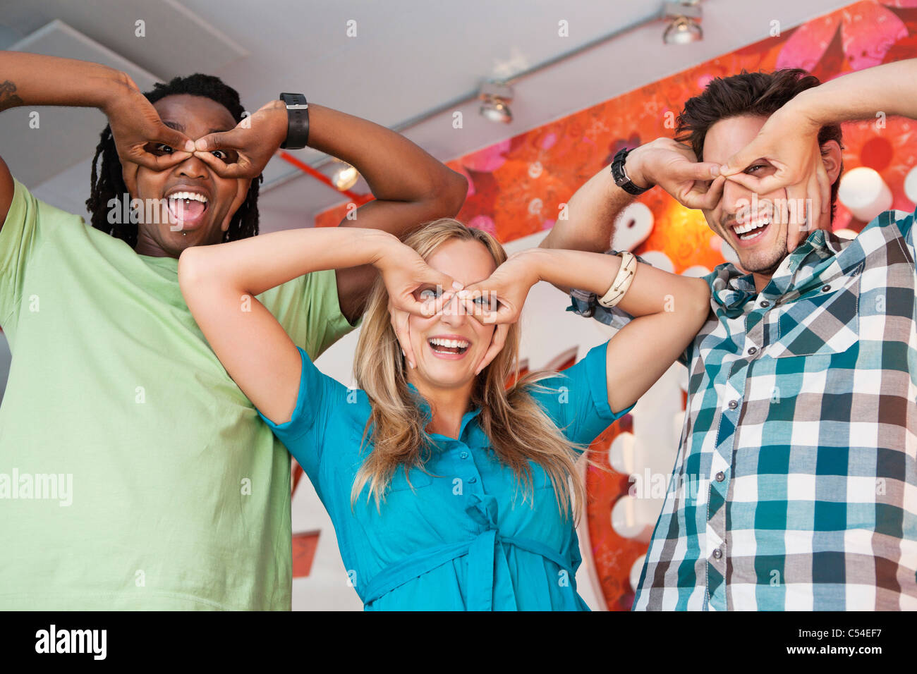 Friends pretending to wear glasses at a bar - Stock Image