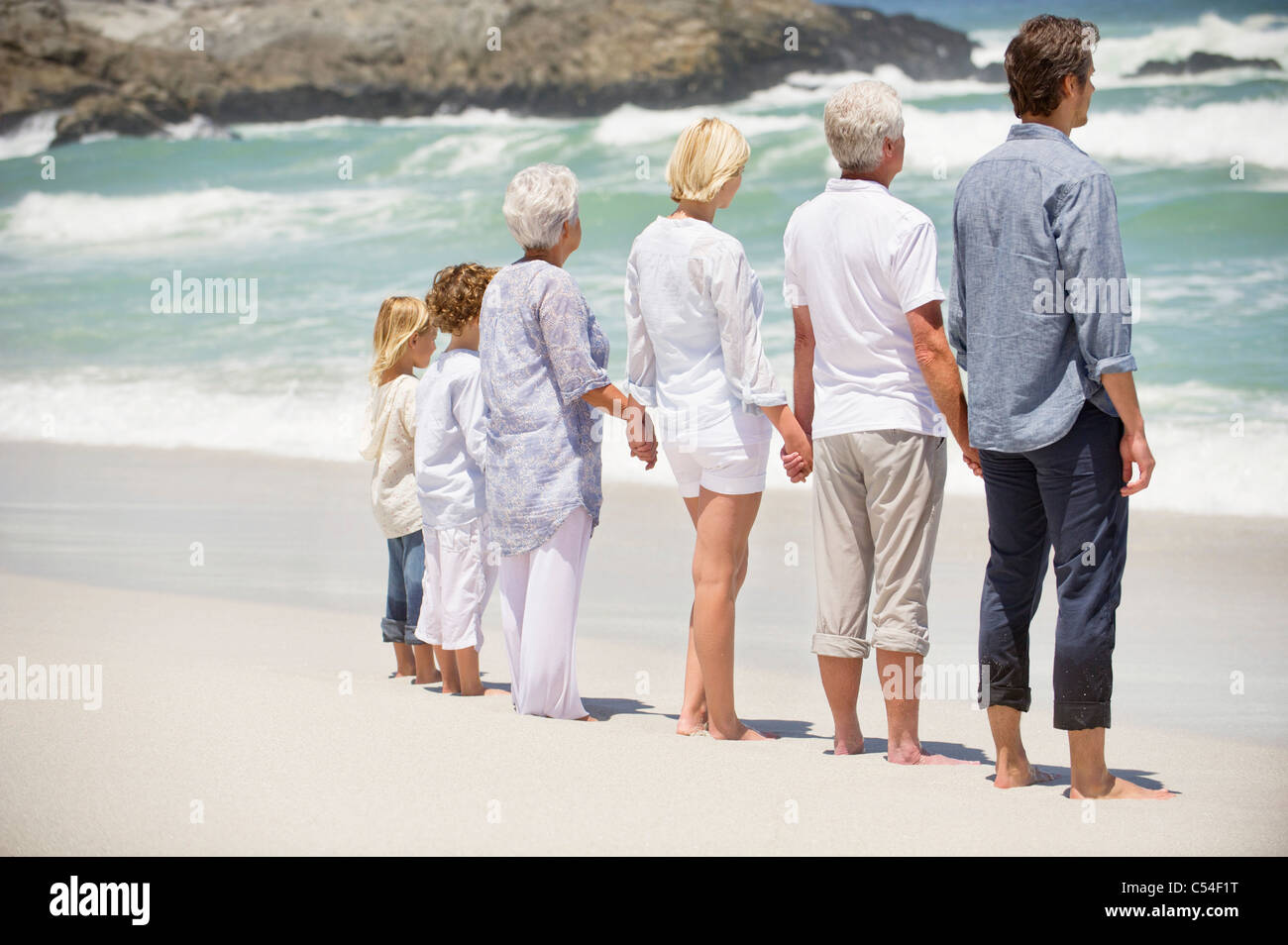 Rear view of a multi generation family standing on the beach - Stock Image