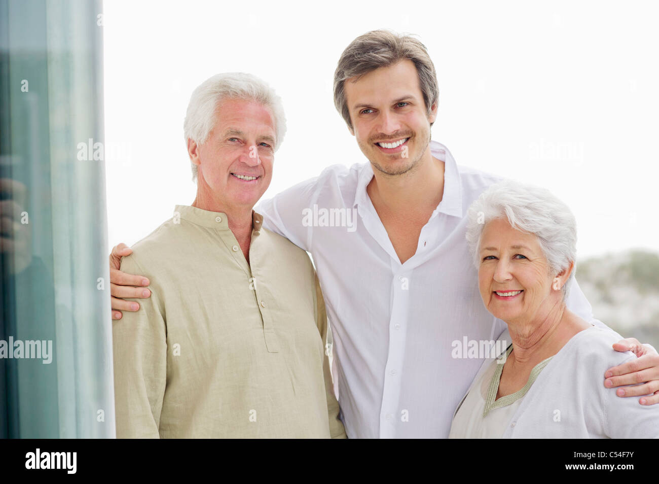 Portrait of a mid adult man standing with his arms around to his parents - Stock Image