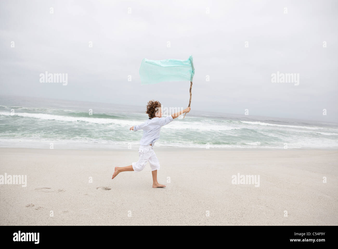 Beautiful view of beach with boy running - Stock Image