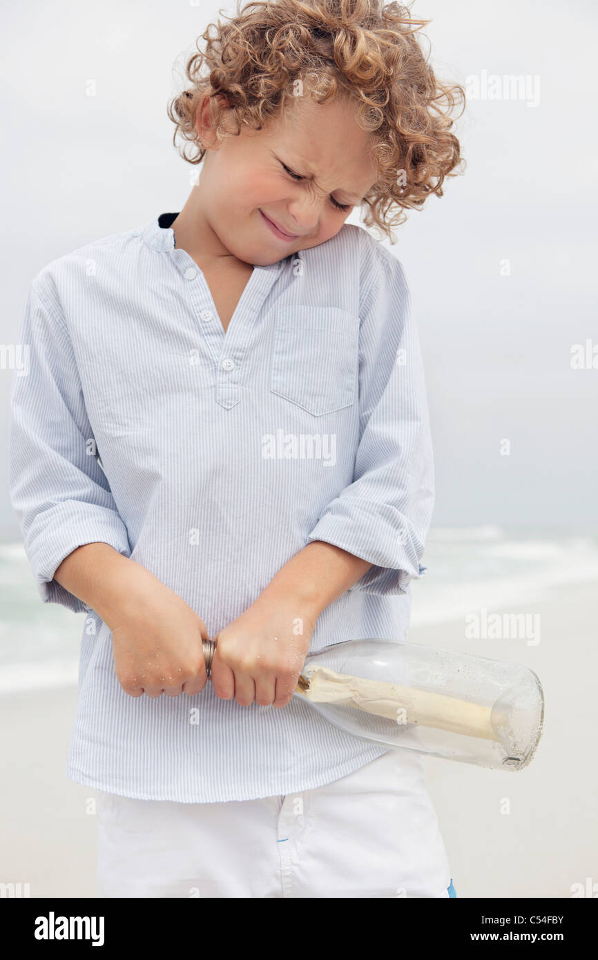 Boy pulling message from a bottle - Stock Image