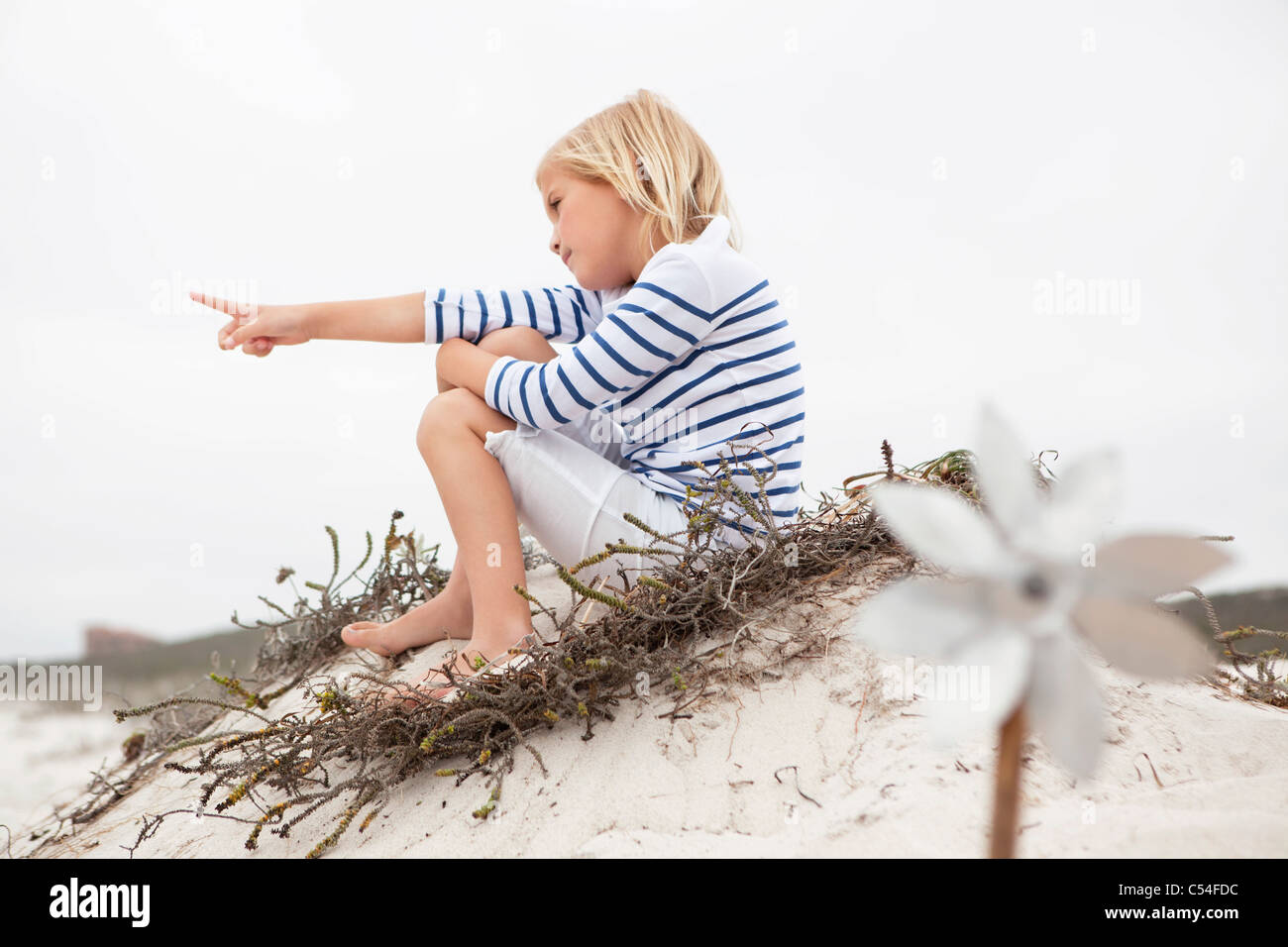 Selective focus of a girl sitting on sand Stock Photo