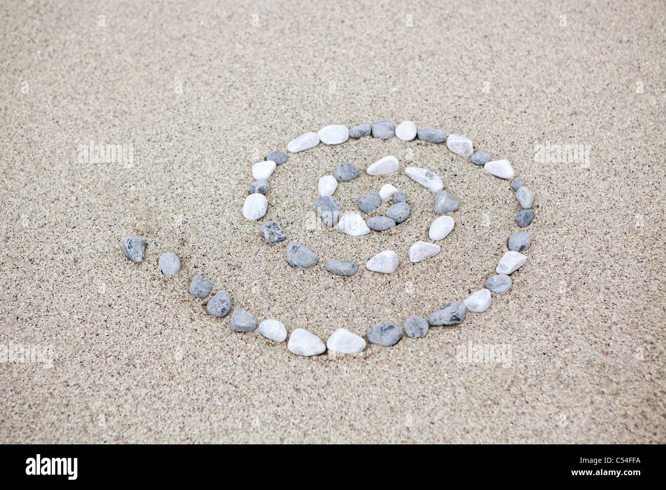 Pebbles arranged in spiral shape on beach - Stock Image