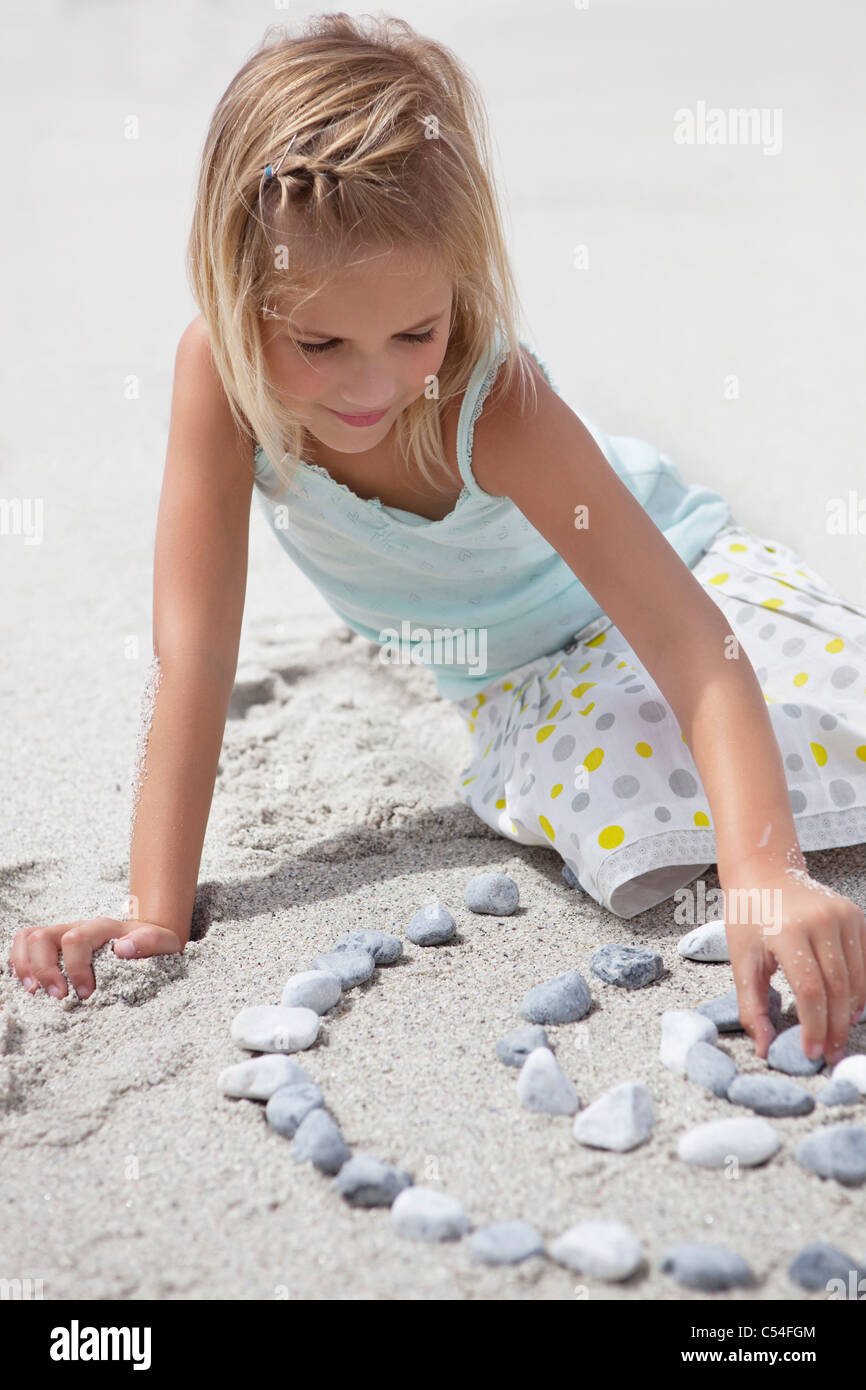 Girl playing with pebbles on beach - Stock Image