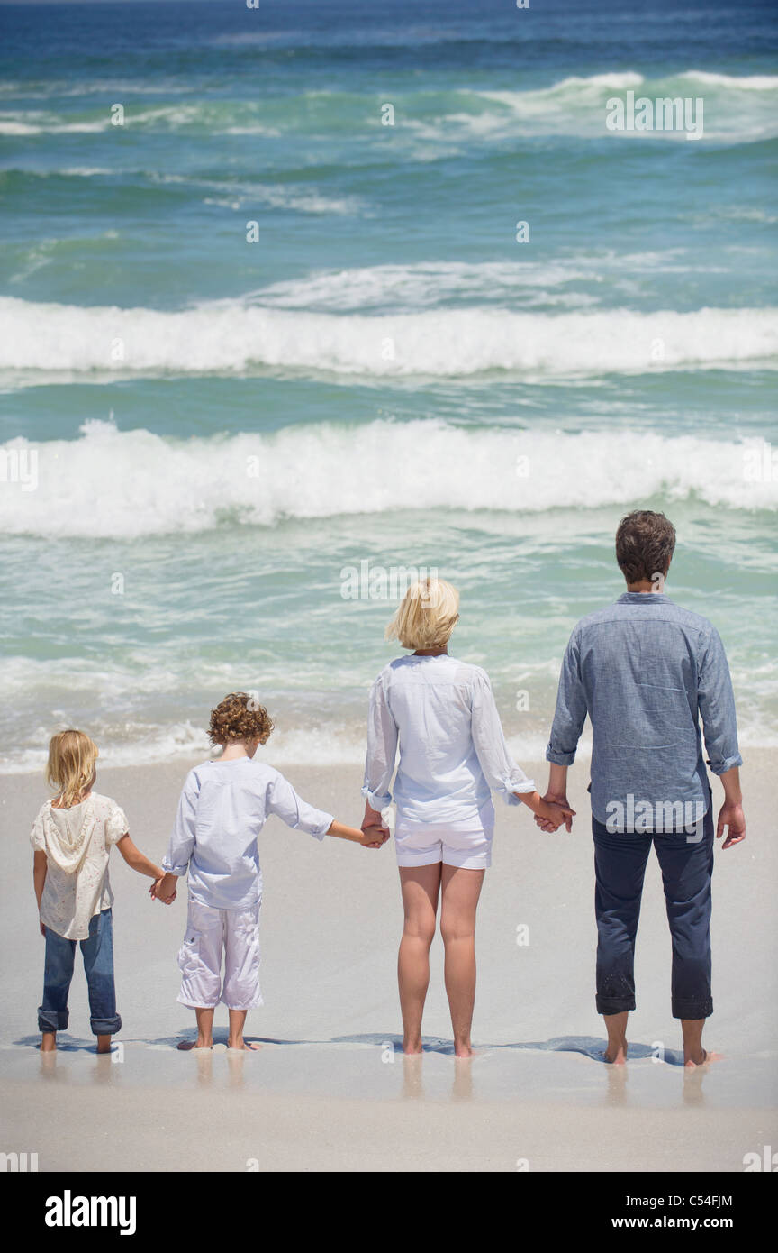 Couple with two children standing on the beach - Stock Image