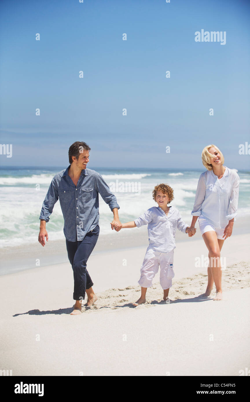 Boy walking with his parents on the beach - Stock Image