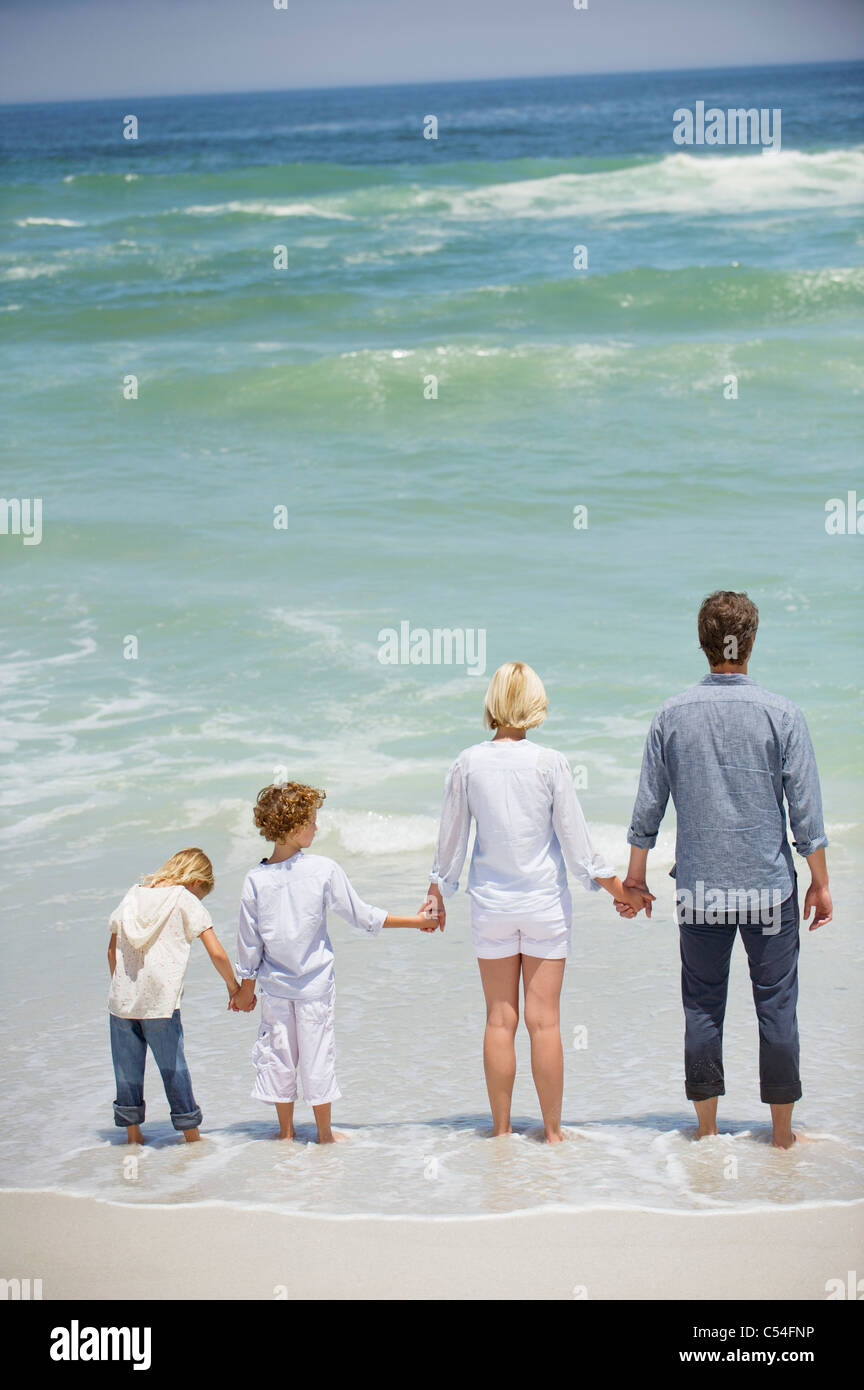 Family with two children standing on the beach - Stock Image