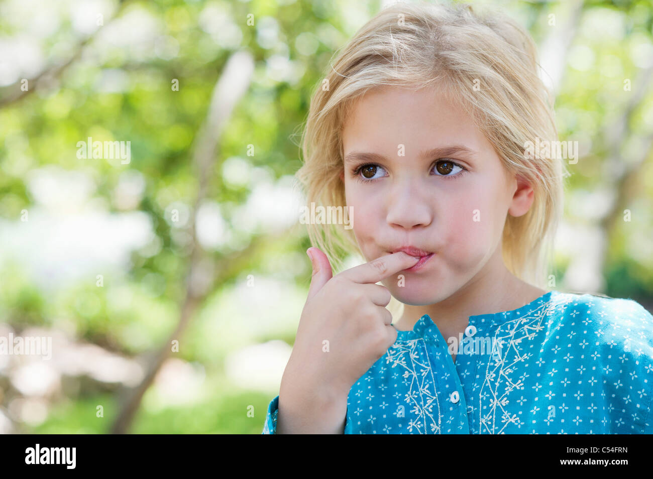 Close-up of a cute girl eating something outdoors - Stock Image