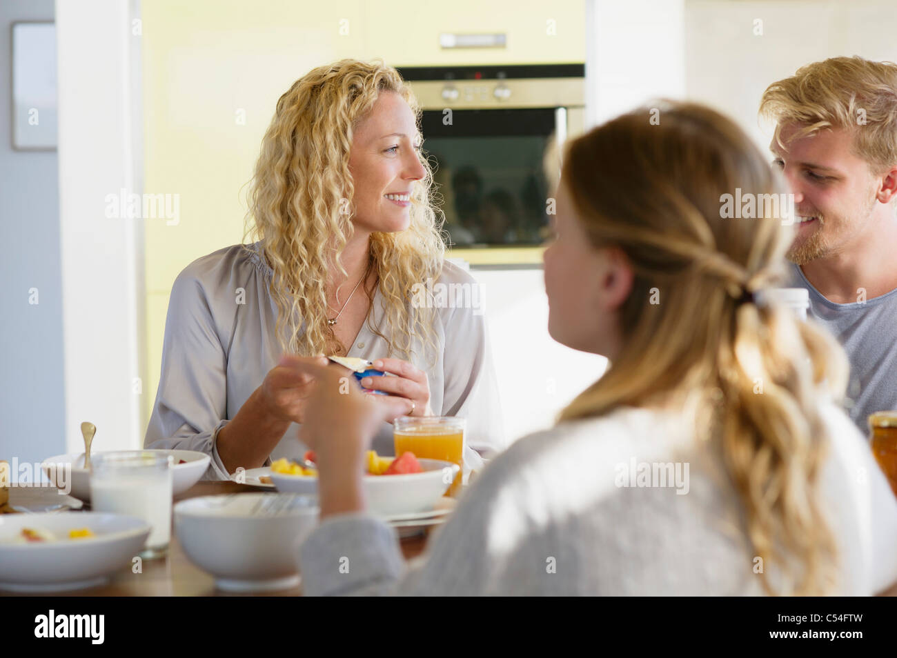 Girl with her parents having breakfast at a dining table - Stock Image
