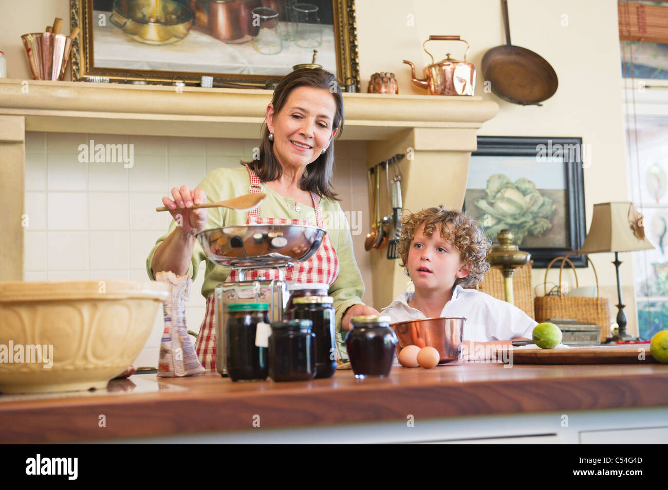Grandmother and little boy cooking food at kitchen - Stock Image