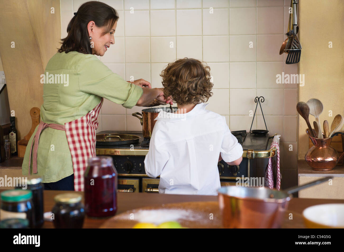 Grandmother and little boy cooking food together at home - Stock Image