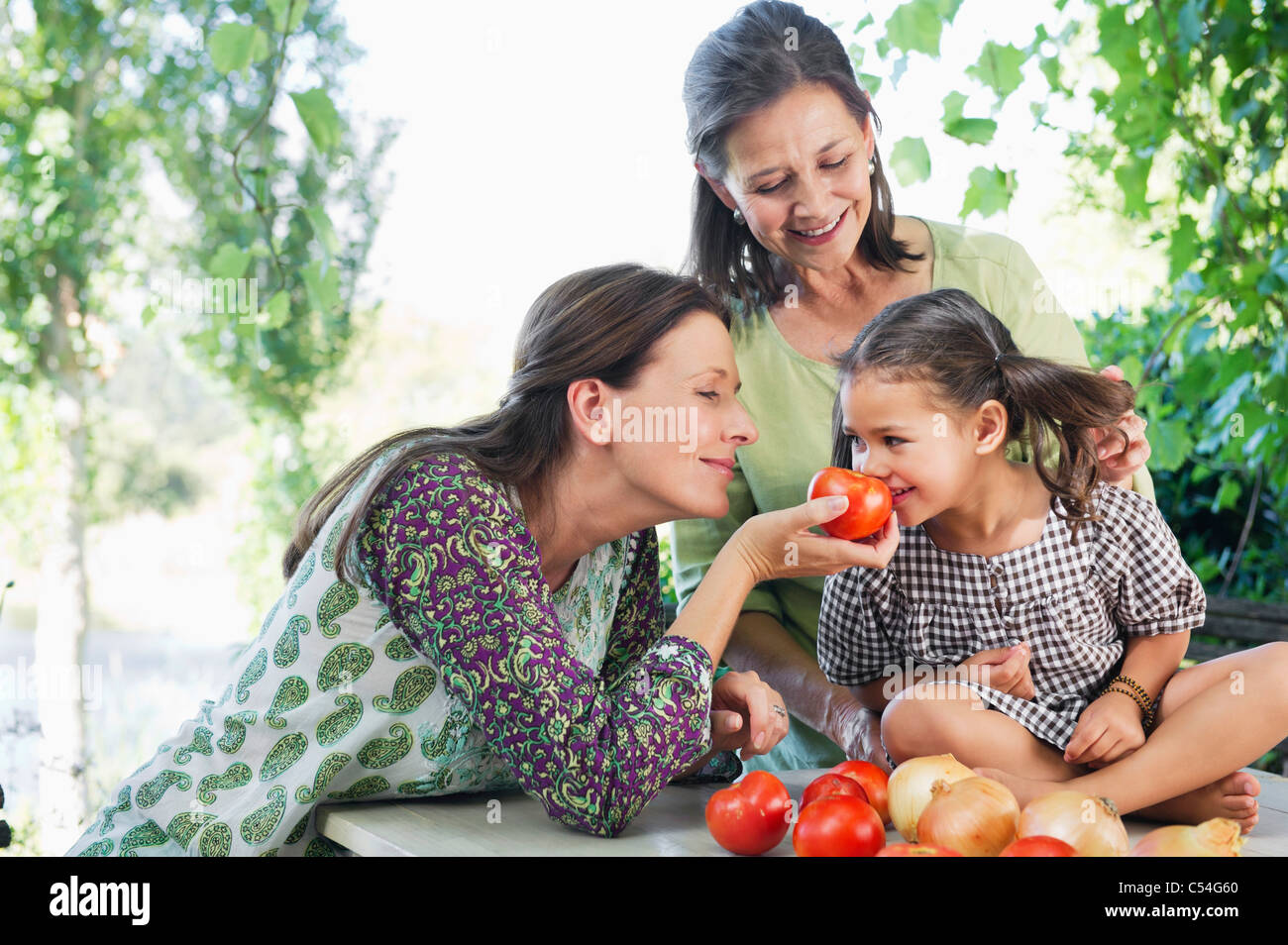 Multi generation family smelling tomatoes - Stock Image