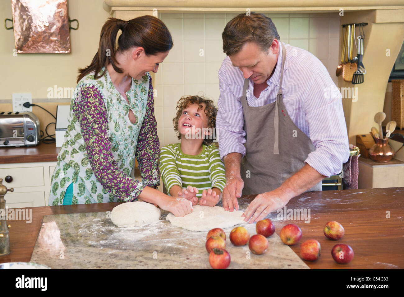 Cute little boy and his parents kneading dough at kitchen - Stock Image