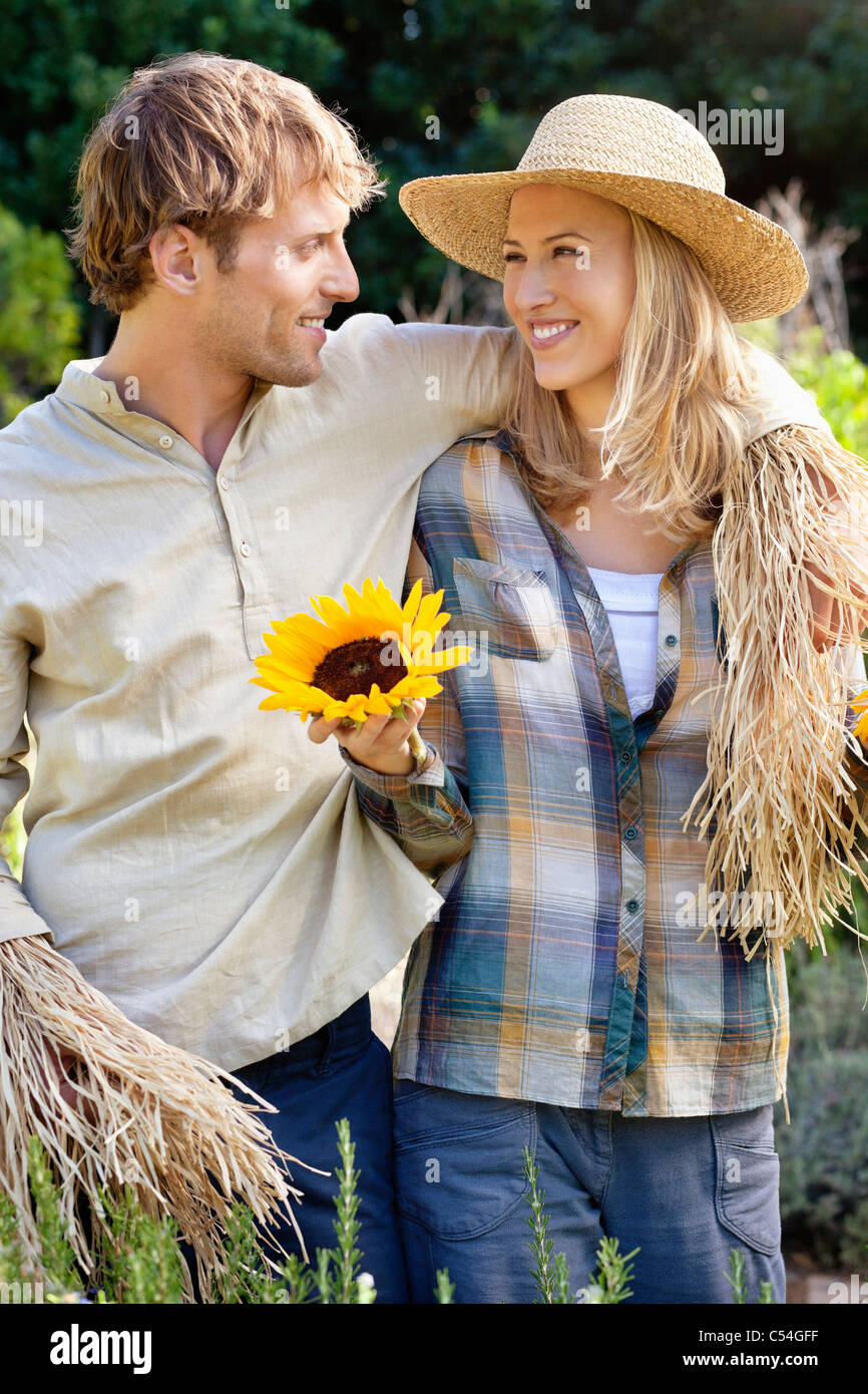 Young couple in scarecrow pose in a field - Stock Image