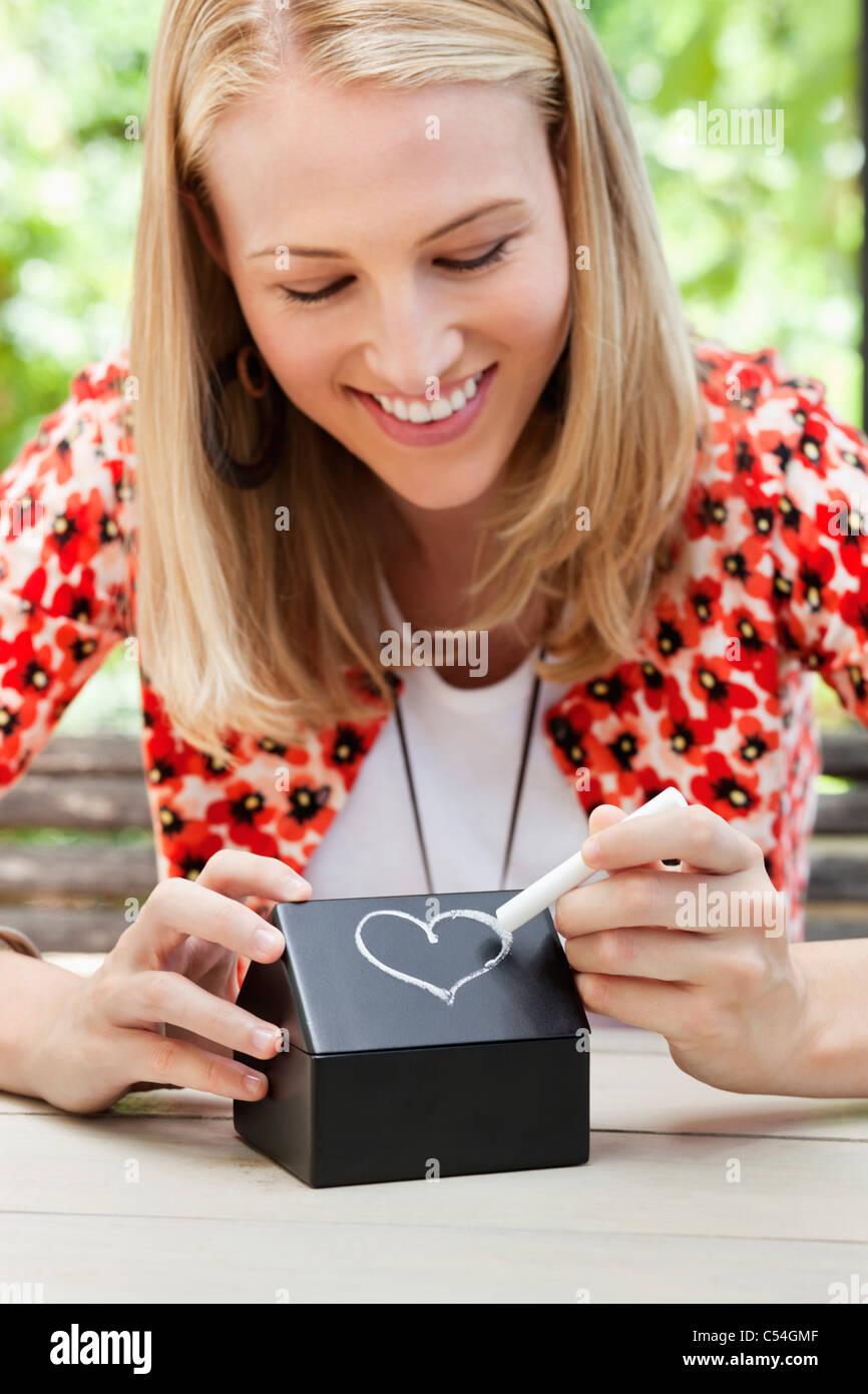 Woman making a heart shape on a model home - Stock Image
