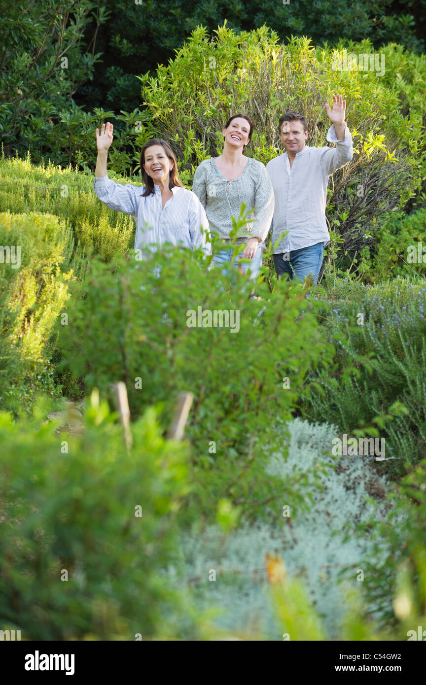 Mature couple walking with their mother and waving hand in a garden Stock Photo