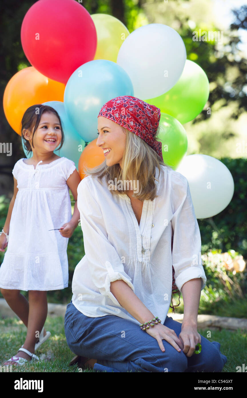 Mother looking at a little girl holding balloons Stock Photo