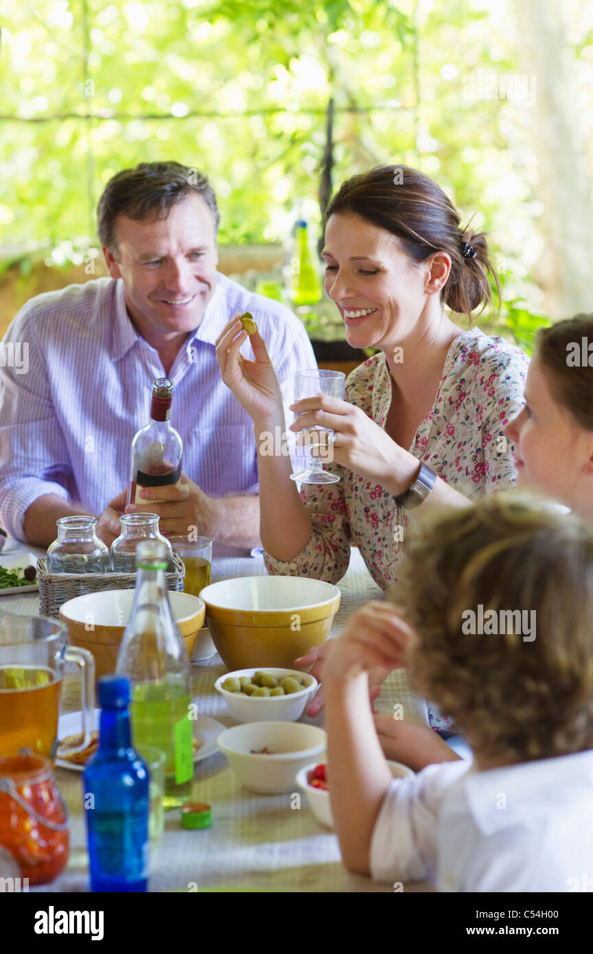 Family having food at home with their two children - Stock Image