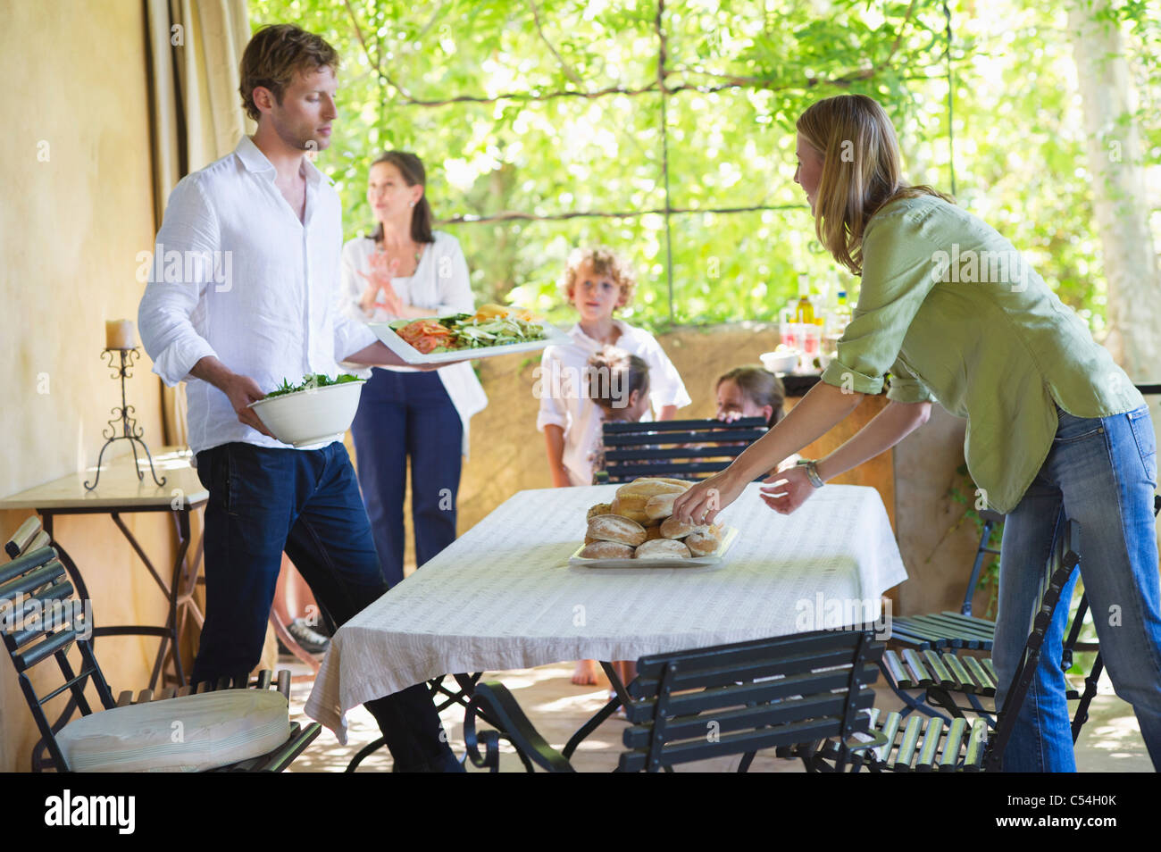Couple arranging food on dining table with family in the background Stock Photo