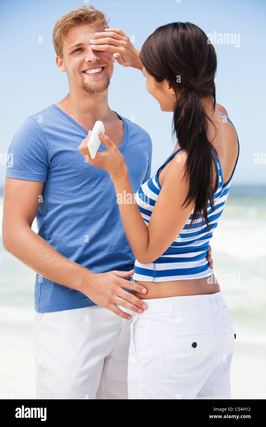 Woman applying suntan lotion on man's face - Stock Image