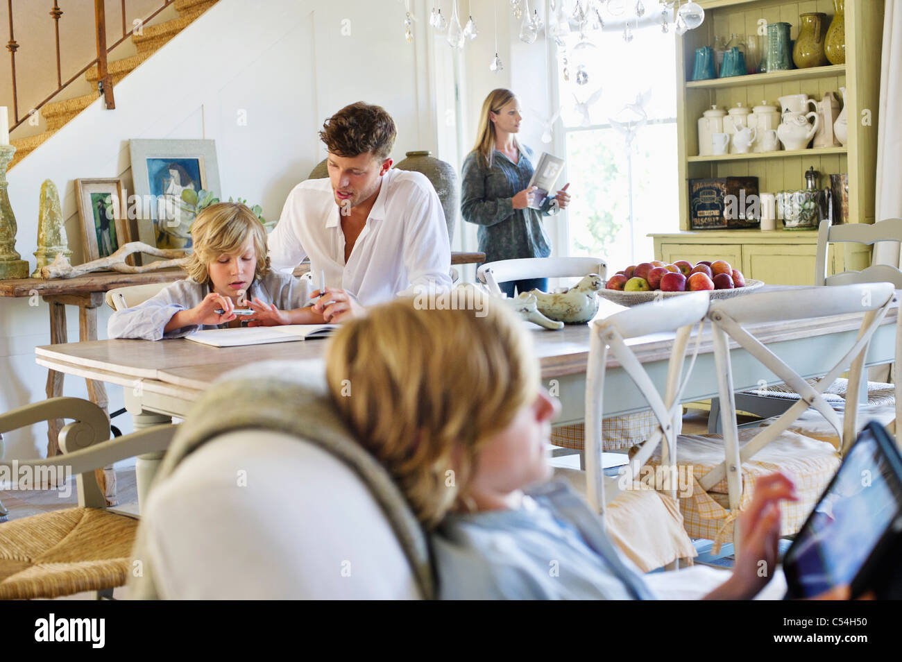 Man teaching little boy while family members busy doing their work at house - Stock Image