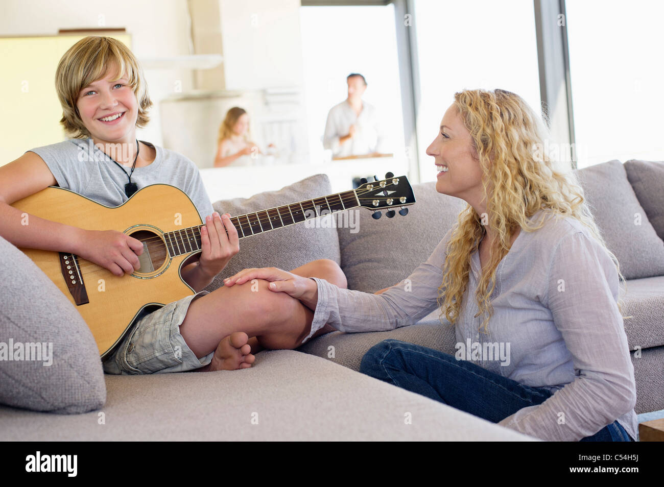 Teenage boy playing a guitar with his mother sitting near him and smiling Stock Photo