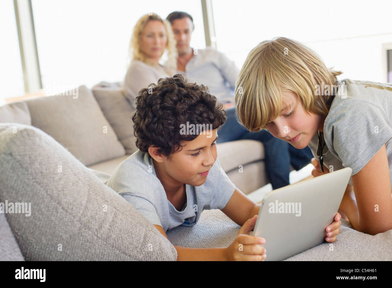 Brothers using a digital tablet with their parents looking at them - Stock Image
