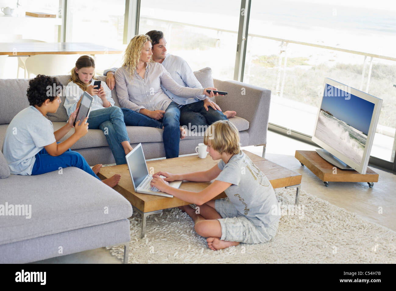 Couple watching television set while their children busy in different activities Stock Photo
