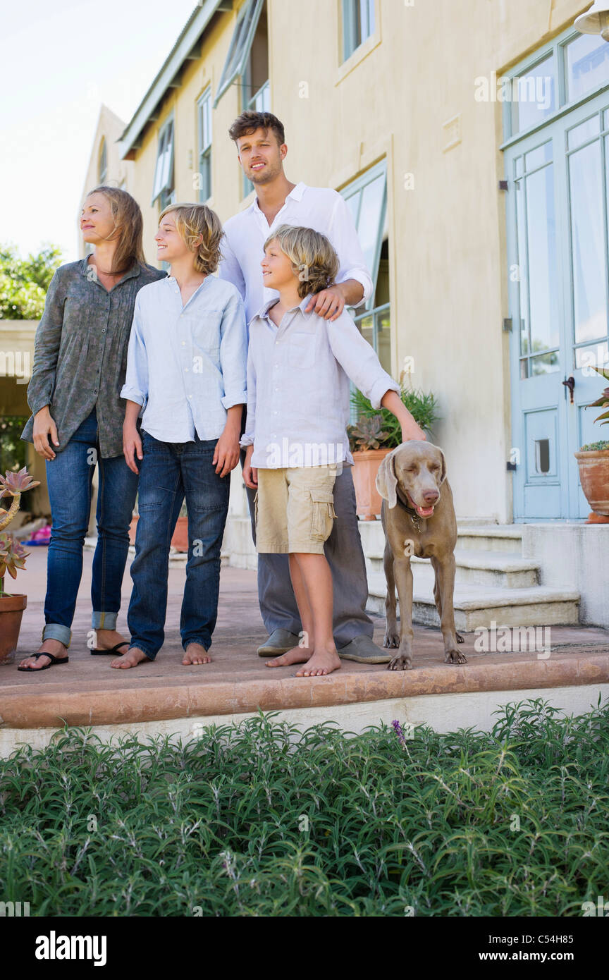 Family standing together with their dog outside house - Stock Image
