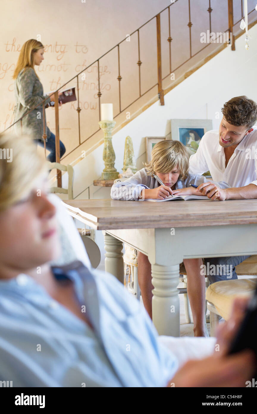 Man teaching little boy with family members busy doing their work - Stock Image