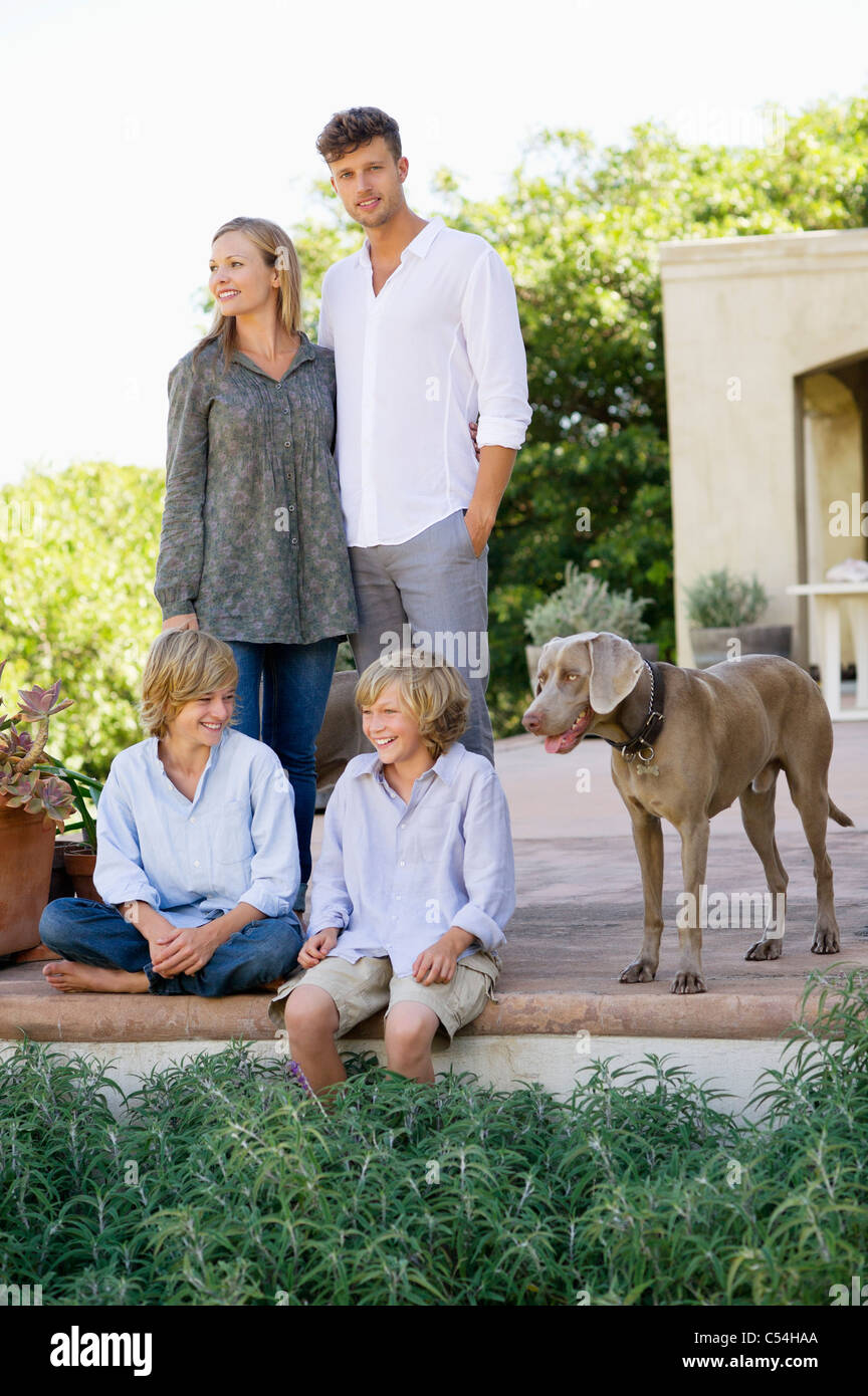 Family with their dog outside house - Stock Image