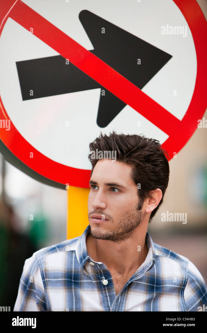 Handsome man thinking with no entry sign in the background - Stock Image
