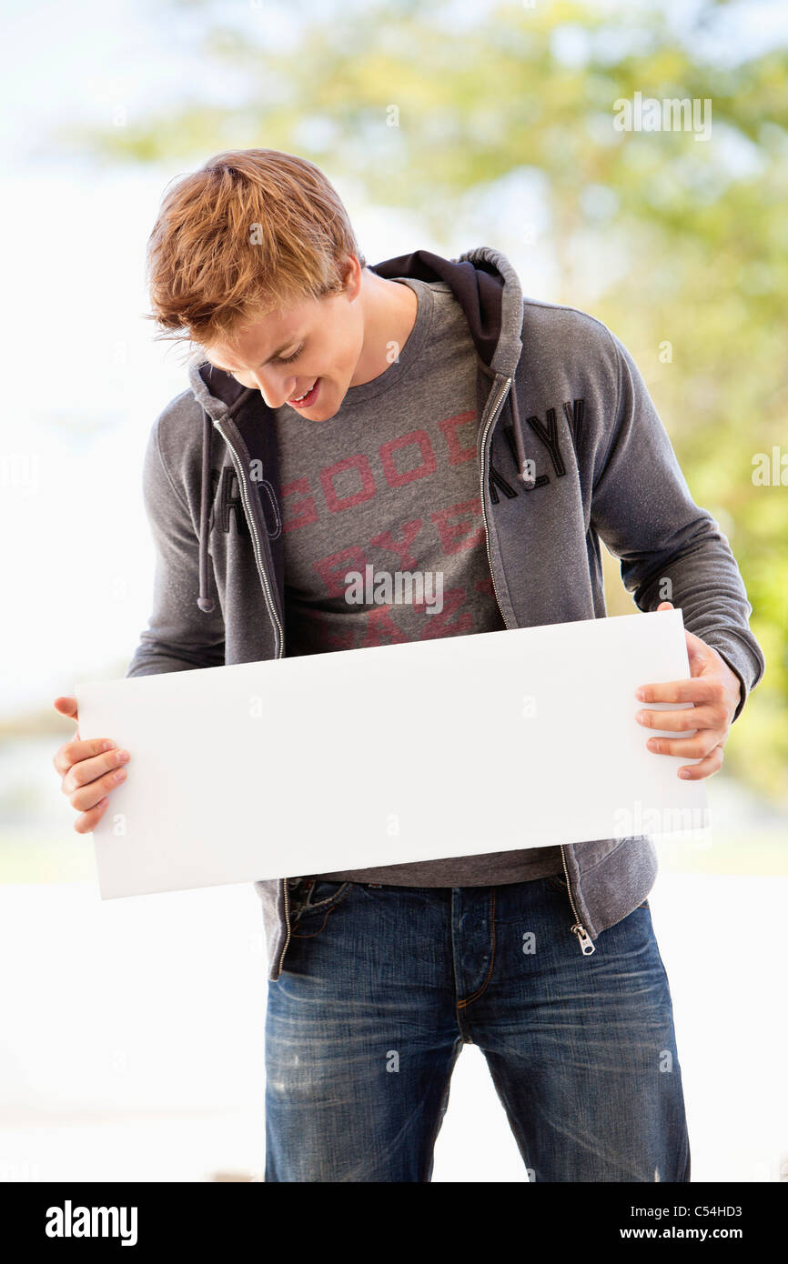 Man looking at a blank placard - Stock Image