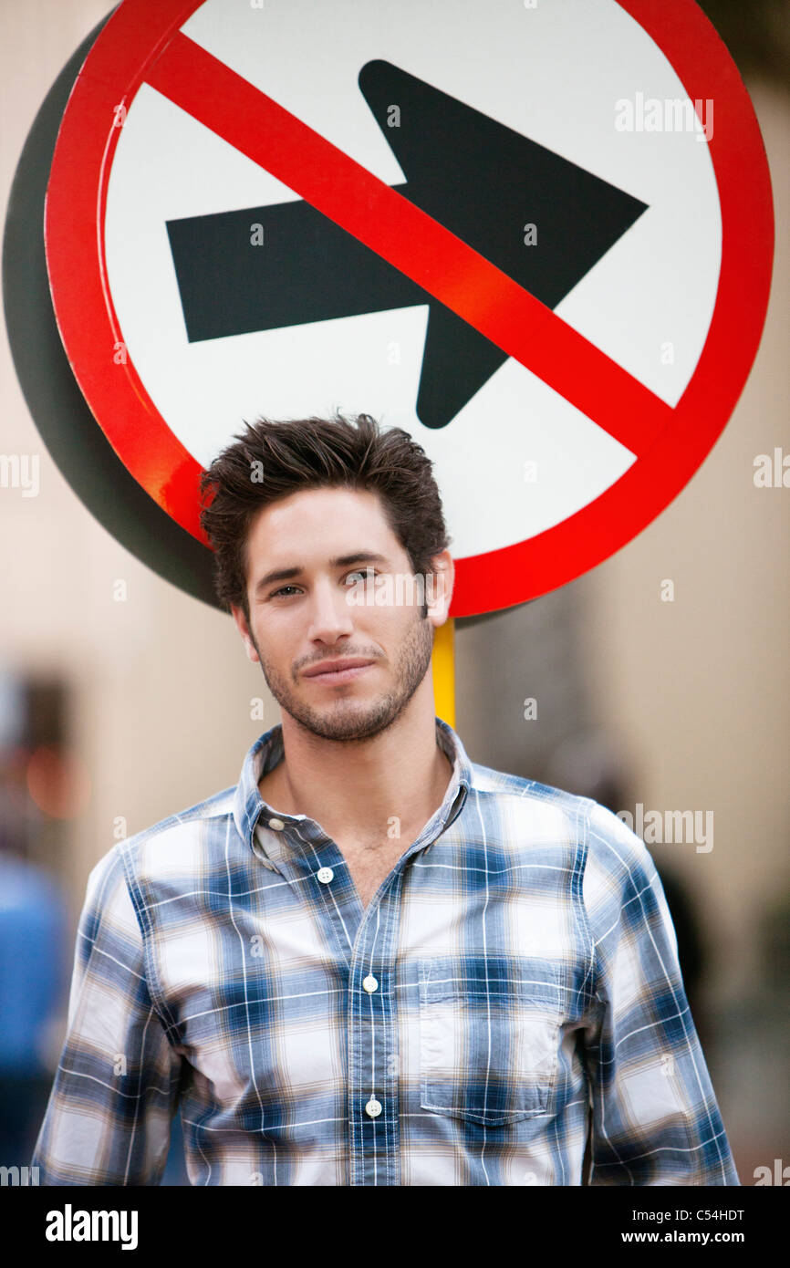 Handsome man smiling with no entry sign in the background - Stock Image